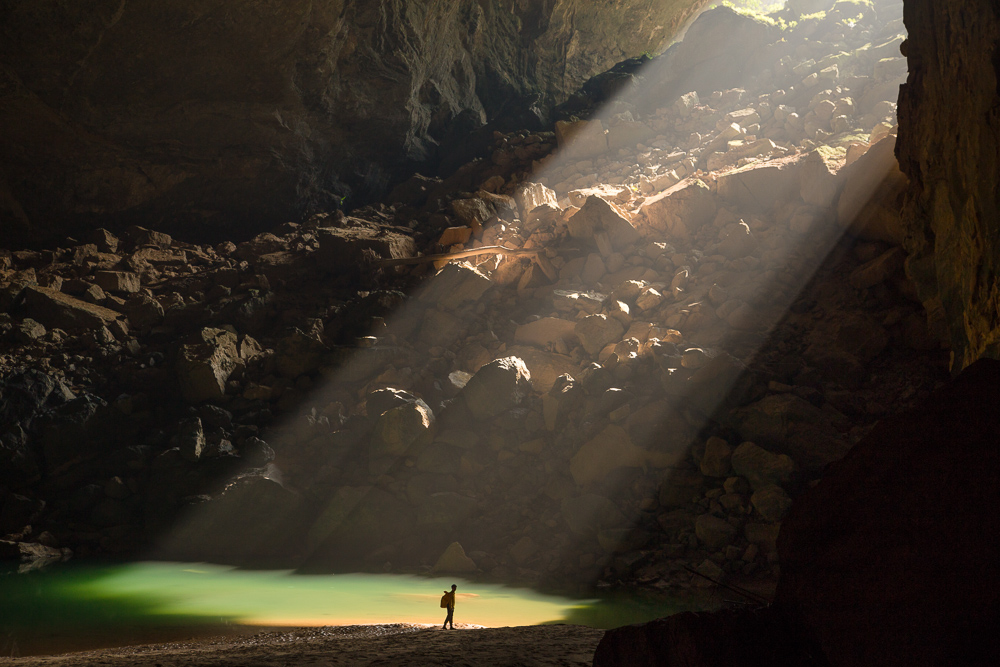 A sunbeam shines in on a caver in Hang En, Phong Nha Ke Bang, Vietnam