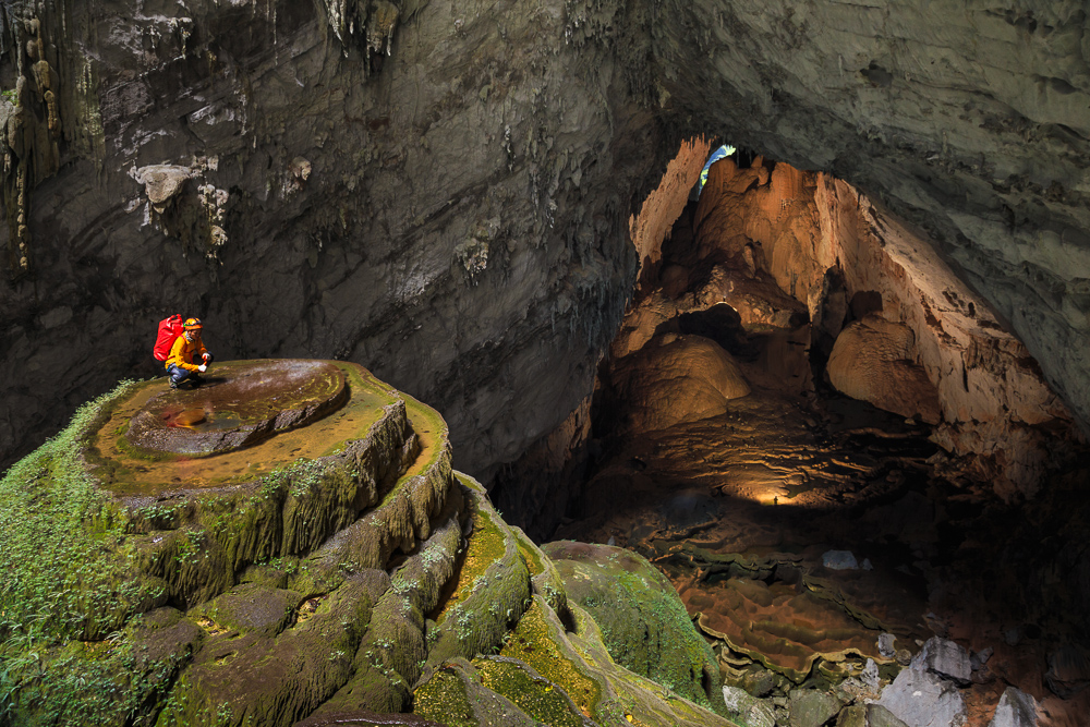 A caver stands at the top for the first doline, better known was Watch Out For Dinosars, in Hang Son Doong, Phong Nha Ke Bang, Vietnam