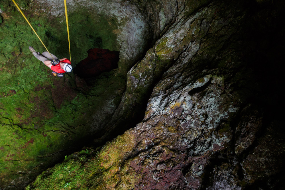 A caver ascends out of a lava tube in Oregon.